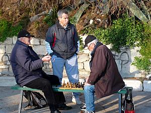 Some young men playing chess on a bench.