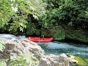 A guide rafting solo through the dangerous part.