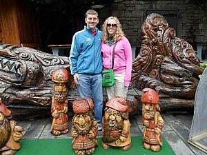 Kevin and Kyleen in front of some fun wood sculptures of the seven dwarves