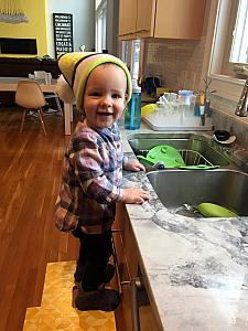 Wearing daddy's hat and playing in the sink
