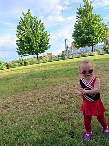 Dressed up in Reds cheerleader outfit as Dad goes to the Reds game. Playing at Christian Moerlein's back lawn.