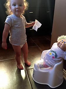 Capri teaching her doll how to use the potty