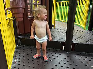 Capri was struggling to climb on the playground in her frilly dress - and didn't like the idea of wearing the backup onesie instead - so, she played on the playground in her diaper :)