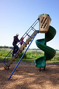 Uncle Jay taking Kenley up the big twisty slide
